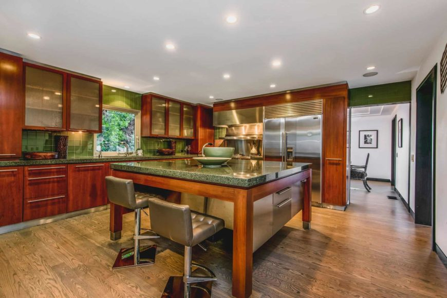 This kitchen features brown cabinetry and brown kitchen counters, along with a center island with a thick granite countertop and has space for a breakfast bar. The area features hardwood floors and a ceiling with recessed ceiling lights.