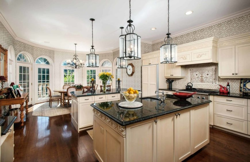 Large dine-in kitchen with elegant walls and backsplash along with hardwood floors. It has a center island and a breakfast bar island, both featuring black granite countertops and lighted by pendant lights.