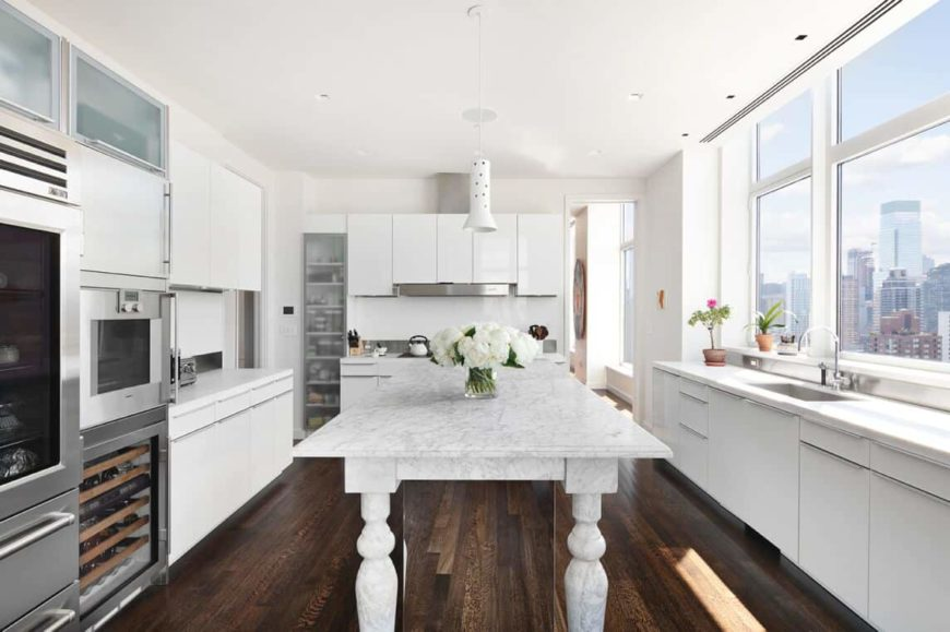 This kitchen offers a classy center island along with white kitchen counters, glass windows and hardwood floors.