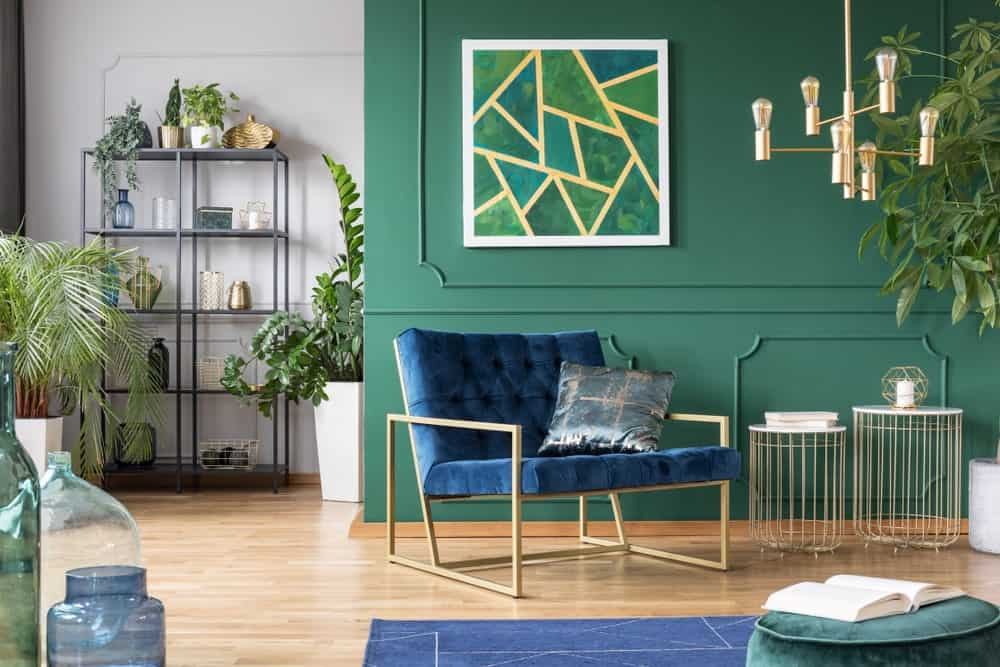 Stylish green living room interior with blue and gold accessories and indoor plants.