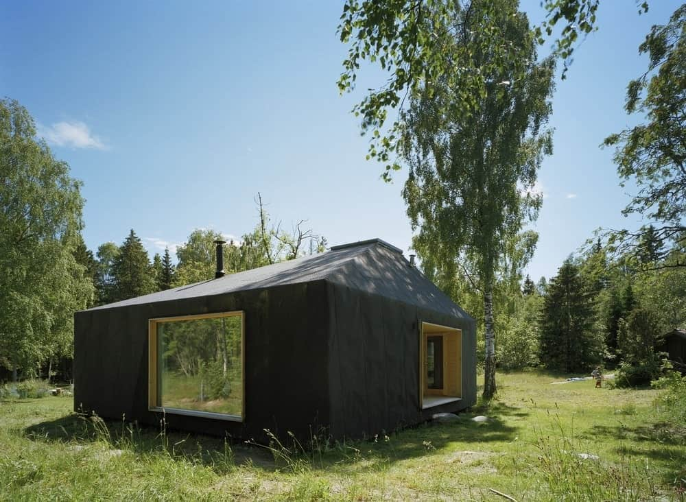 This is a charming and small cottage in the middle of the clearing of the forest filled with tall pine trees and wild grass. Its black exterior walls and large glass windows make it stand out amidst the surrounding greenery of the clearing.