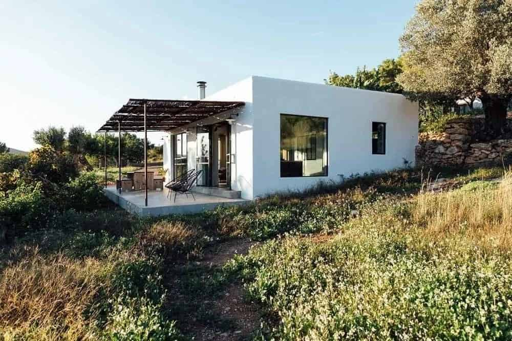 A gorgeous and simple small house with white exterior walls making it stand out in the middle of its rustic landscape surrounding. It has an outdoor dining area and sitting area under wooden covers to better immerse with the landscape.