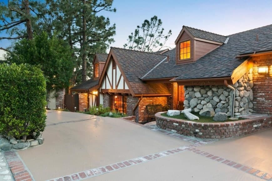 This lovely Cottage-style has a warm charming quality to its stone walls, brick planters, brick exterior walls and the dark earthy hue of its roofing that goes perfectly well with the warm yellow lights of the interiors escaping through the windows matching the outdoor lighting.