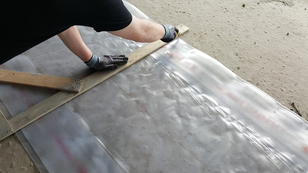 A worker cutting sheet with knife to fit the window.