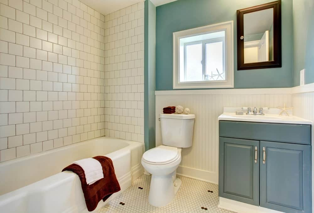 Three-quarter bath with white brick and blue walls, drop-in tub, toilet, sink vanity against beadboard walls, hex tile flooring and black framed mirror contrasting the white framed window.