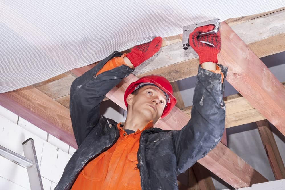 Builder attaching vapor barrier to wooden beams on the ceiling.