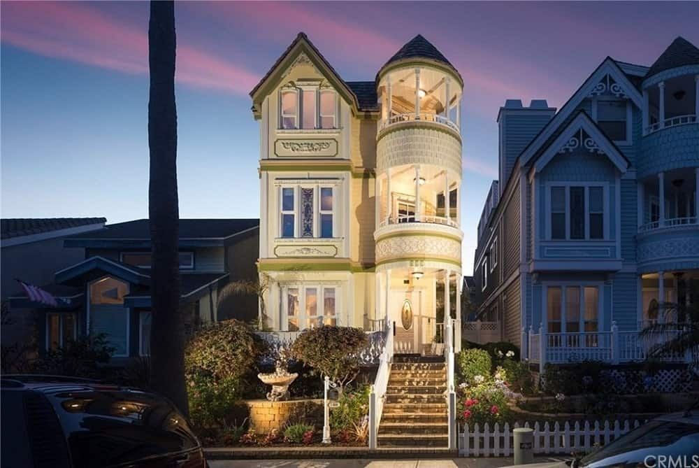 This lovely and charming Victorian-Style home has three stories of lovely sunny yellow exterior walls complemented by the outdoor lighting directed at the house making it glow warmly. There is a small front yard fitted with a small garden and a stone fountain beside a set of steps leading up to the entryway.