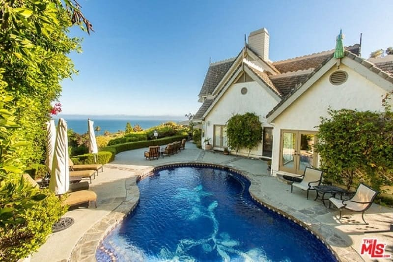 This Victorian-Style home has textured beige exterior walls and dark brown roofing. These are complemented by the tall shrubs planted by the walls to add a bit of color along with the pool at the backyard with a nice view of the sea through the hedges.
