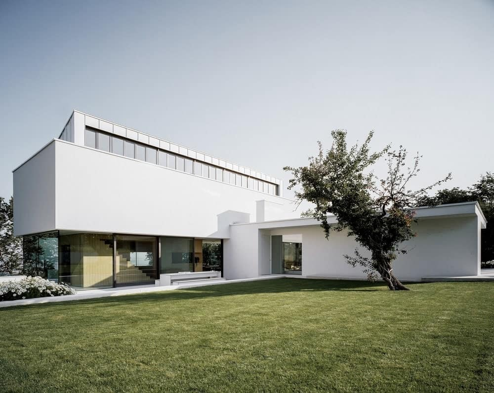 The brilliant white exterior walls of this modern home is complemented by its abundant glass walls and windows that look out over the charming lawn of grass in the backyard perfect for those home parties and gatherings decorated with a single tall tree in the middle.