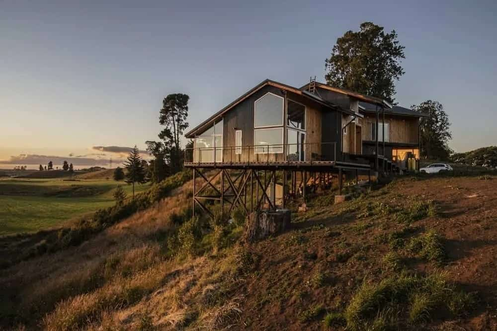 This is such a peaceful and tranquil home located on a slope looking down on a vast plain. This view is maximized by the house's large glass windows and glass walls that elevates the rustic vibe of the home exterior.