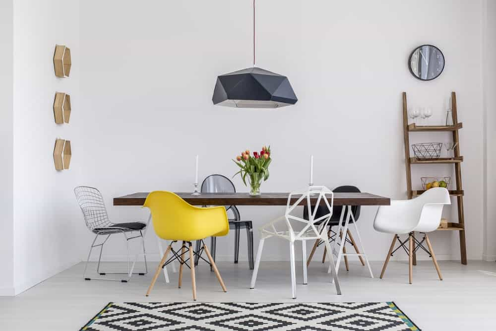 White dining room with light hardwood flooring topped by a patterned rug, hexagonal shelving, wooden ladder, rectangular dining table paired with mismatched chairs and a black geometric pendant light.