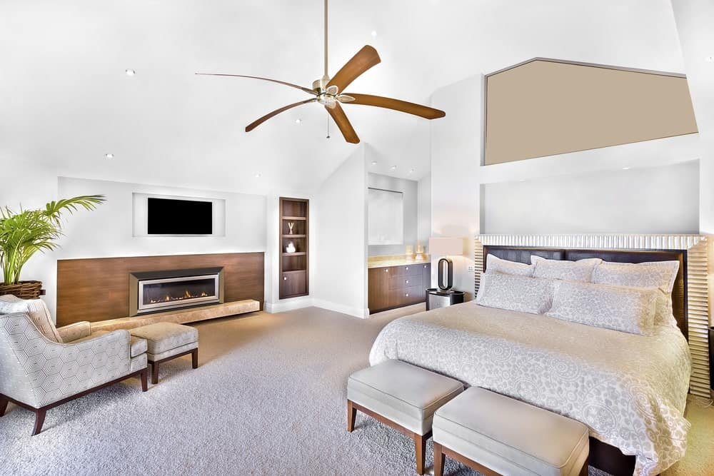 White primary bedroom with vaulted ceiling, carpet flooring, comfy bed with footstools, modern fireplace, wall TV, chaise lounge, ceiling fan and vanity area.