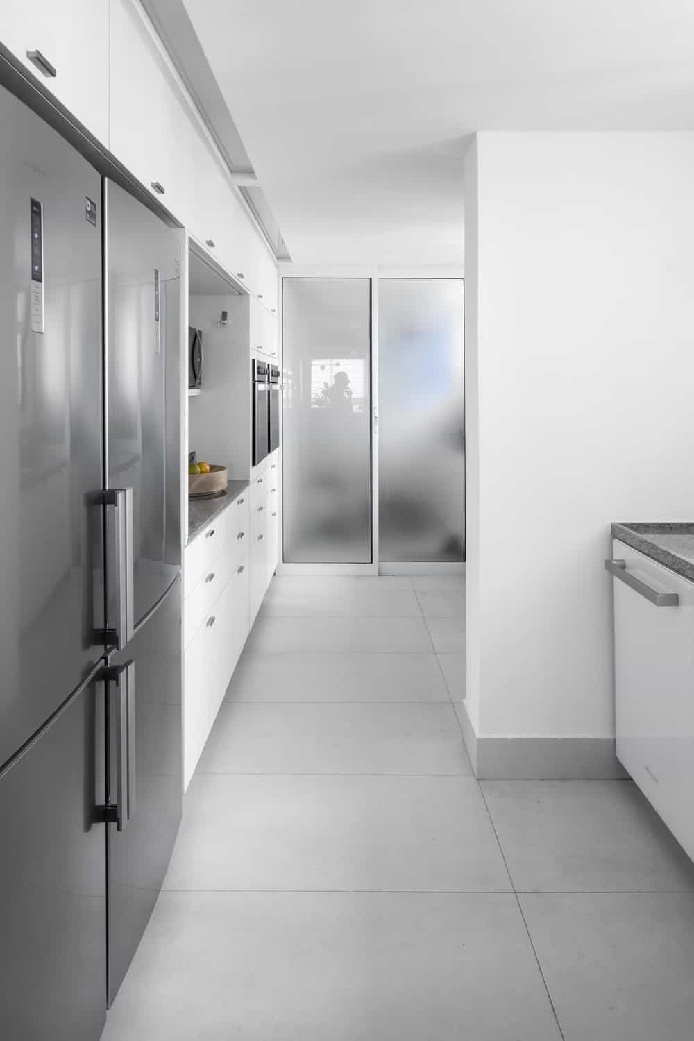 This is a close look at the long and narrow kitchen with white cabinetry that makes the stainless steel appliances stand out.