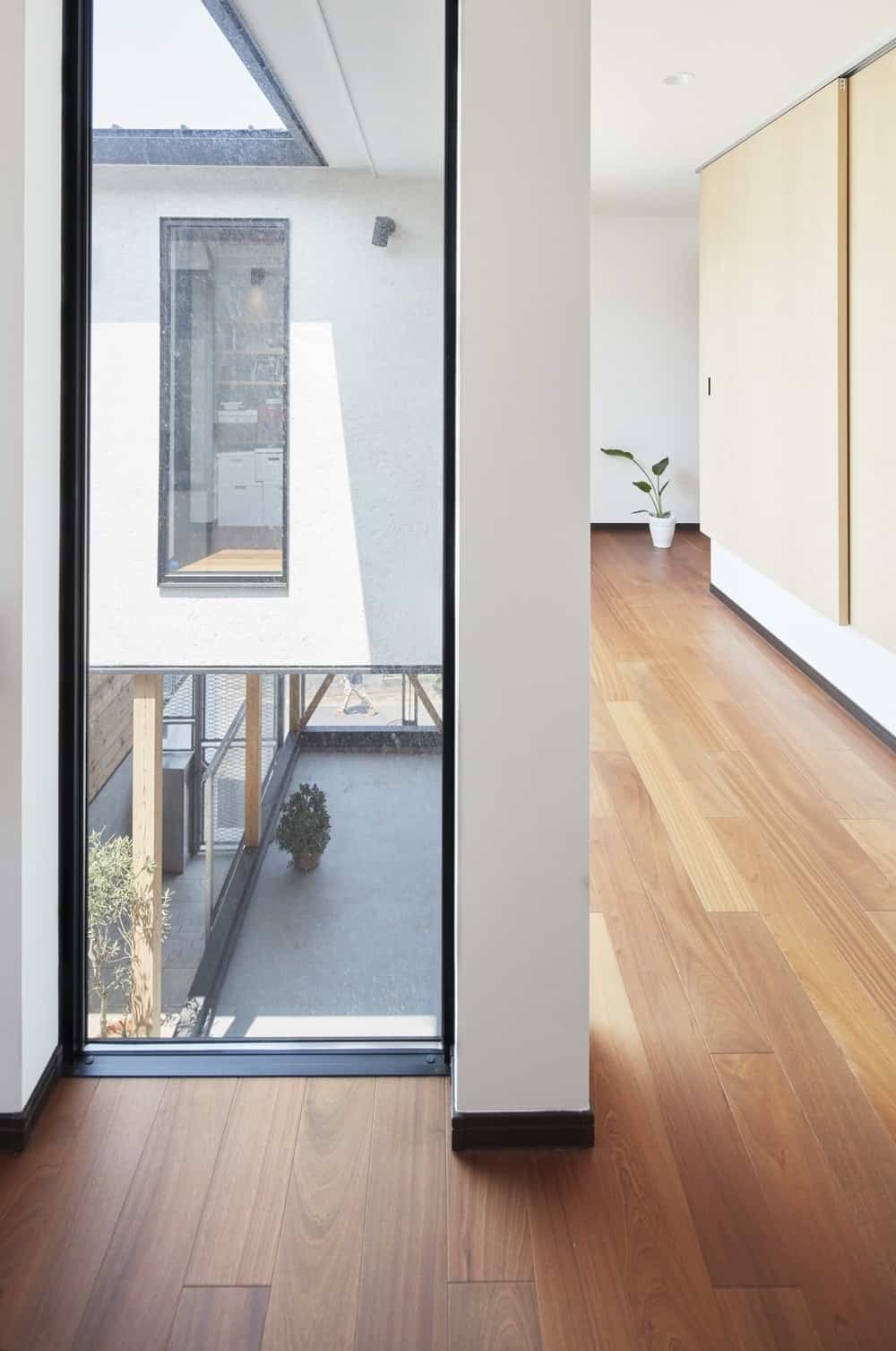 Hallway and full height window in the Triple Stilt House designed by Archidance.