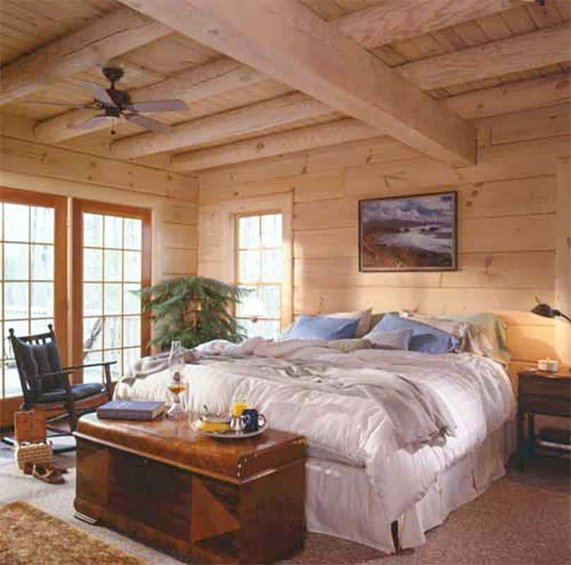 Maser bedroom with beam ceiling, wood siding, and access to the deck.