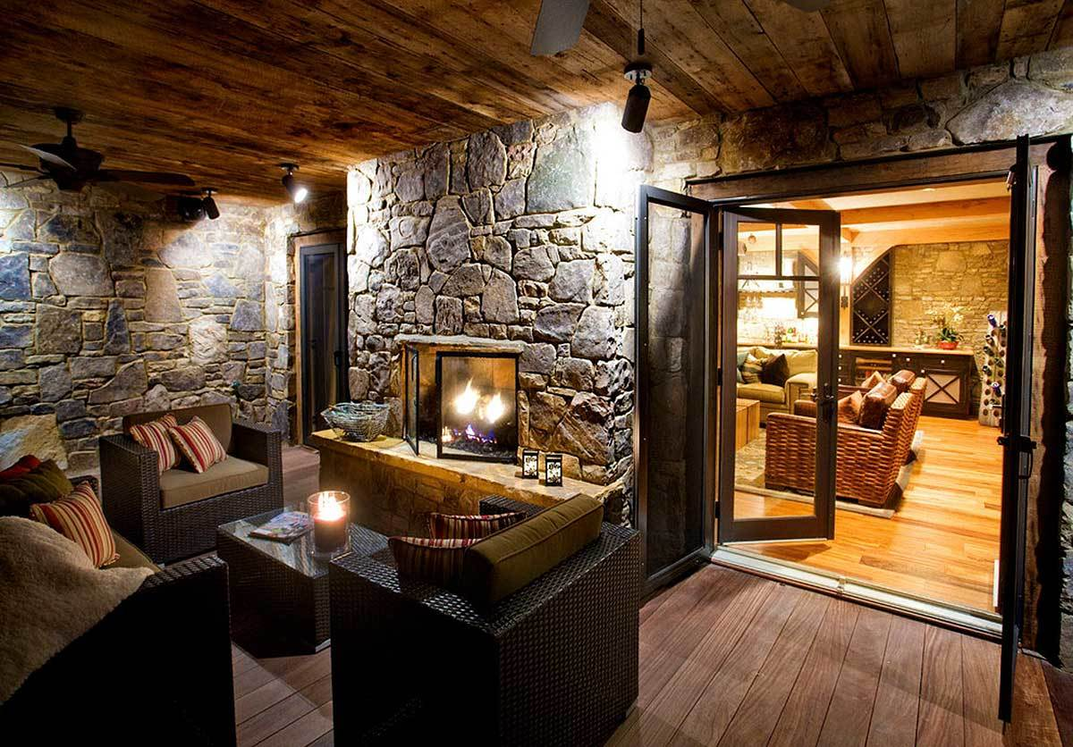 Covered patio with beam ceiling, stone wall facade, and an outdoor stone fireplace.