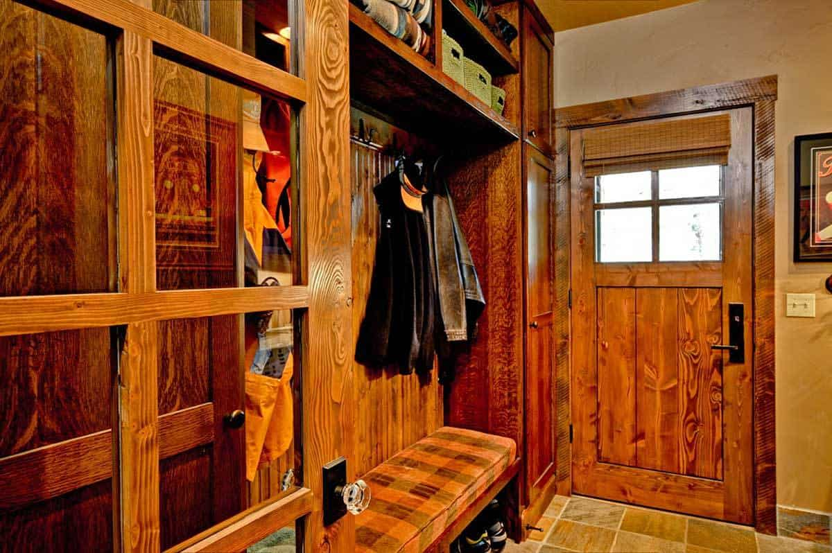 This hallway is filled with built-in storages and a cushioned bench that doubles as a shoe rack.