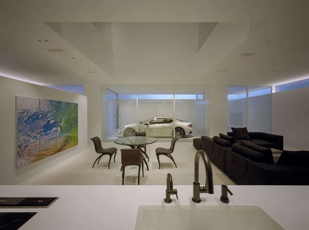 Living room, dining area and kitchen overlooking the garage in the House in Takamatsu designed by Fujiwaramuro Architects.