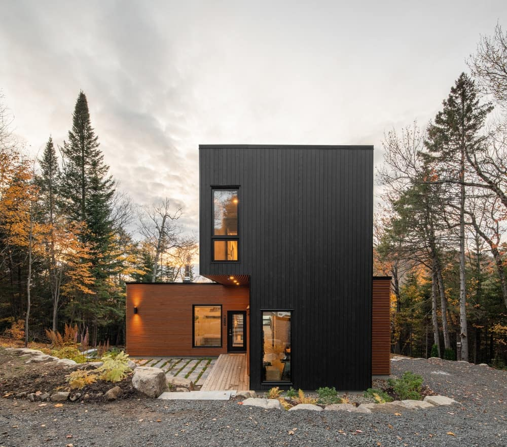 This is a front view of the house that has two tones with wood and black exterior walls complemented by the warm windows.