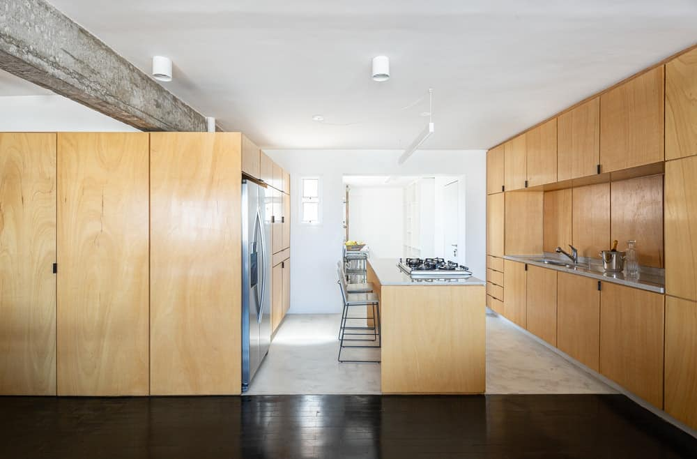 This is a view of the kitchen showcasing the large wooden structures on either side of the wooden kitchen island. These structures houses the appliances along with built-in cabinets and shelves.