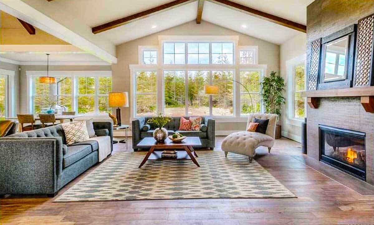 The home's living area has cozy tufted seats and a patterned area rug that lays on the natural hardwood flooring.