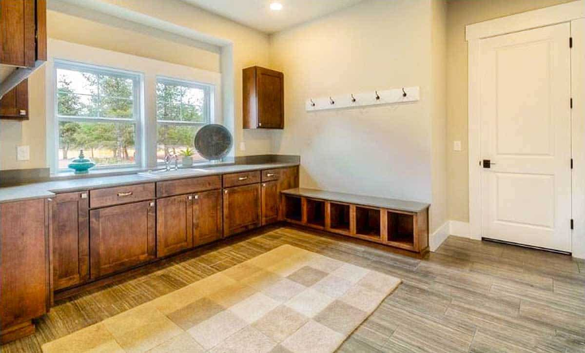 The spacious pantry has rustic cabinets and a large checkered rug over the hardwood flooring.
