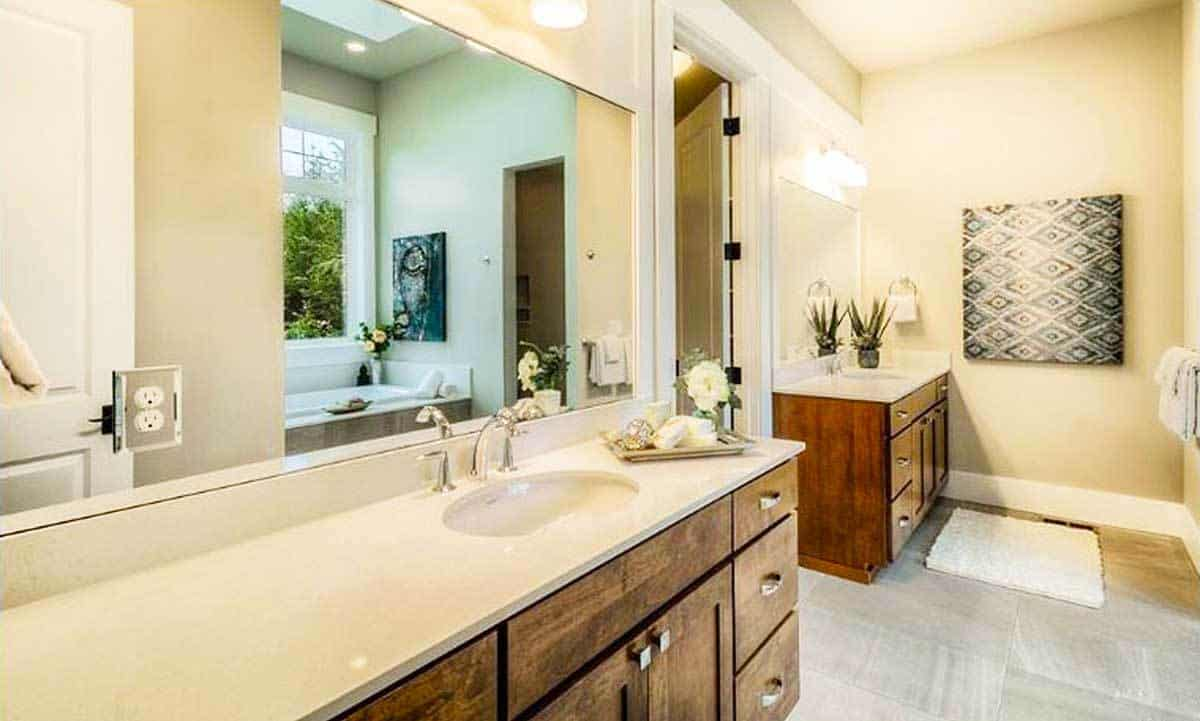 The primary bathroom features two vanities fixed against the beige walls adorned by a patterned artwork.