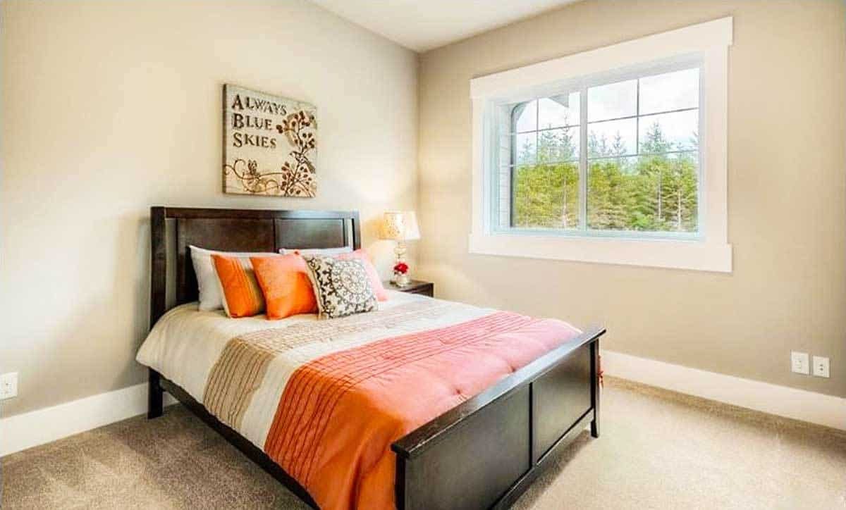 This bedroom has a dark wood nightstand matching the bed that's dressed in bold striped bedding.