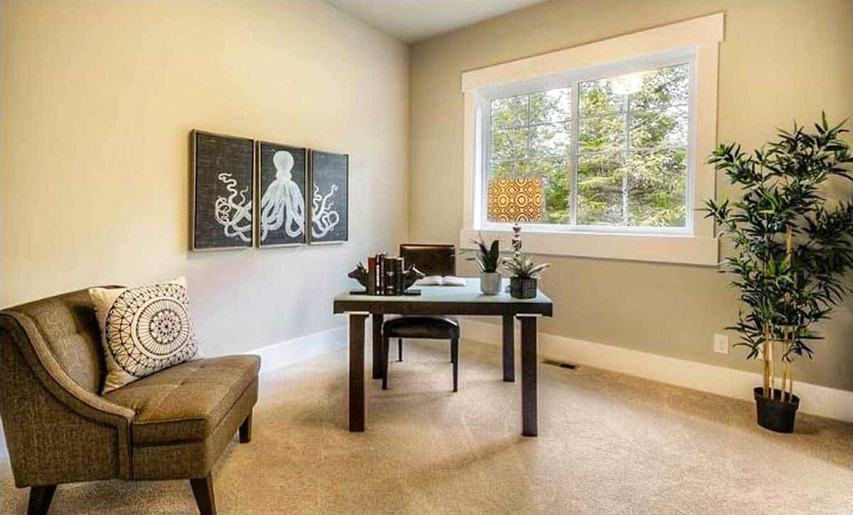 The home office boasts a sleek, tufted seat and a dark wood desk paired with a leather chair.