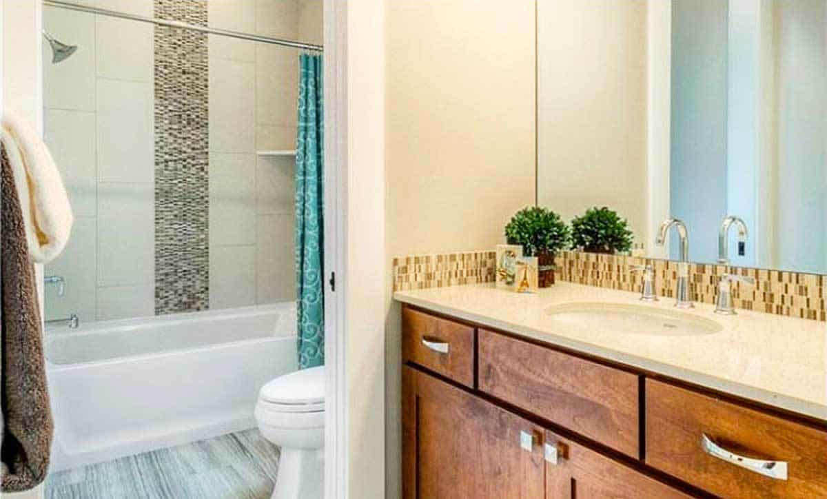 The other bathroom has a wooden vanity, a toilet, and a shower and tub combo enclosed in a patterned curtain.