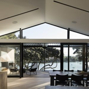 Dining area overlooking the patio and lake view in the Herne Bay Hideaway designed by Lloyd Hartley Architects.