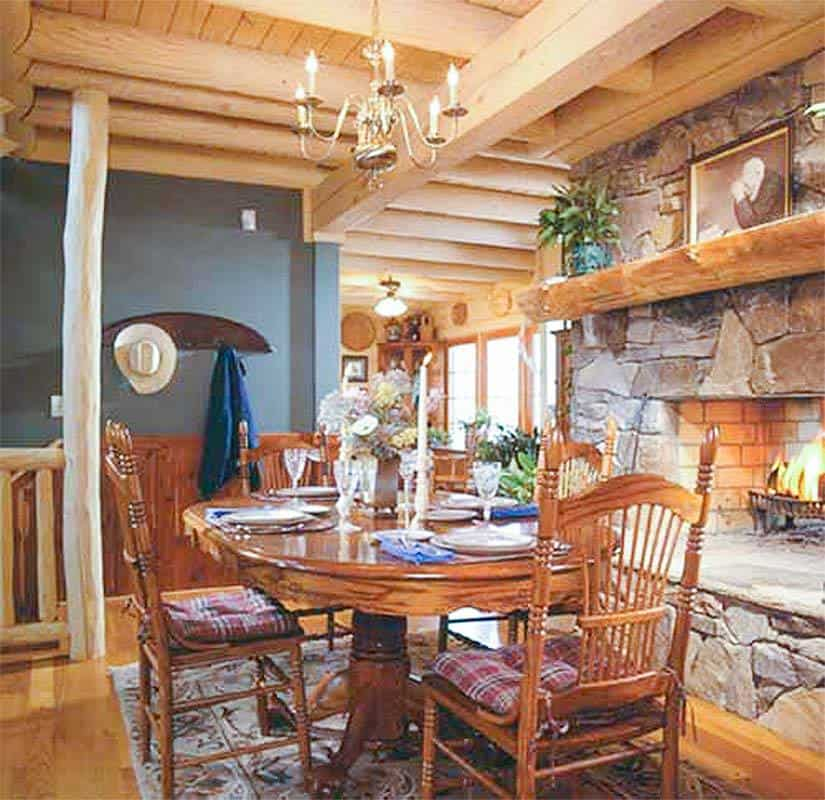 The dining room is crowned by log ceiling and chandelier and faces the stone fireplace.