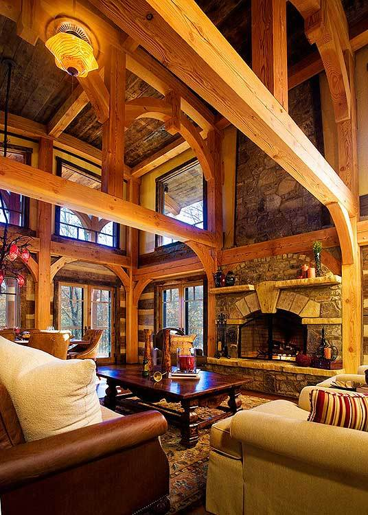 Spacious living room with stone fireplace topped with a high ceiling and soaring arched timber bents.