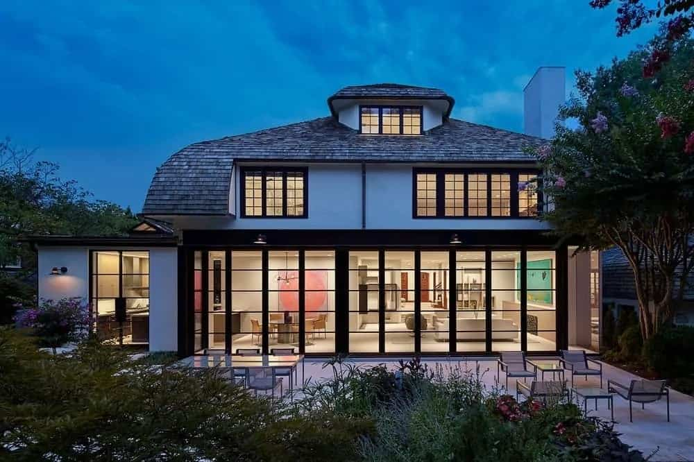 The house has an abundant amount of glass walls and windows that have frames and grids to create a unique look that glows at night from the warmth of the interior lights.