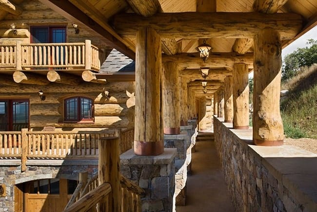 The breezeway has a cathedral ceiling supported by large wood beams with stone bases. Warm pendant lights hang over the concrete flooring.