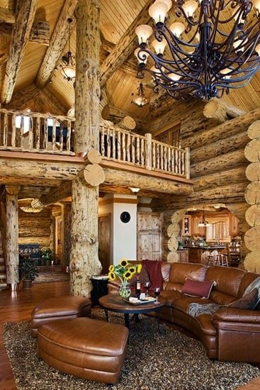 The opposite side view of the great room shows the open loft supported by large, rustic wood columns.