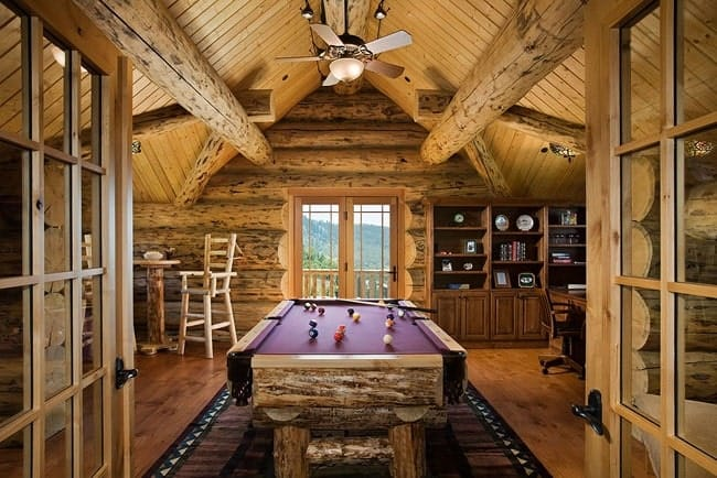 The french door opens to the game room with a billiards table, sitting area and a fan hanging from the cathedral ceiling.