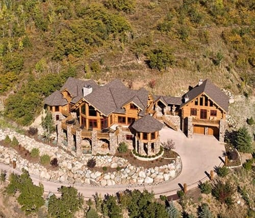 Aerial view shows the classic gable roofing and marvelous landscaping featuring large stones that complement well with the log home.
