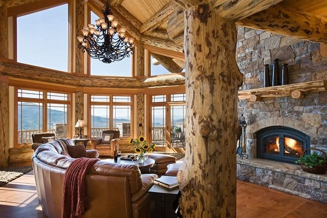 The great room has a stone fireplace, cozy leather seats, grand wrought iron chandelier and massive glass windows overlooking the surrounding mountains.