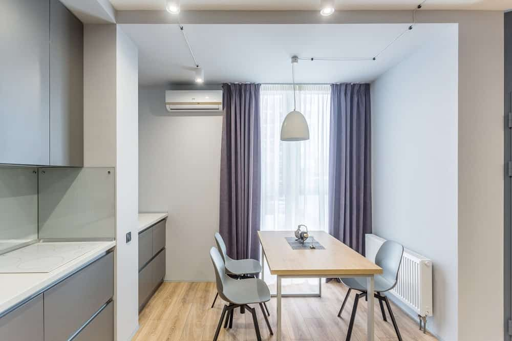This is a look at the informal dining area by the kitchen illuminated by the tall window that brighten the wooden table and light gray tones.
