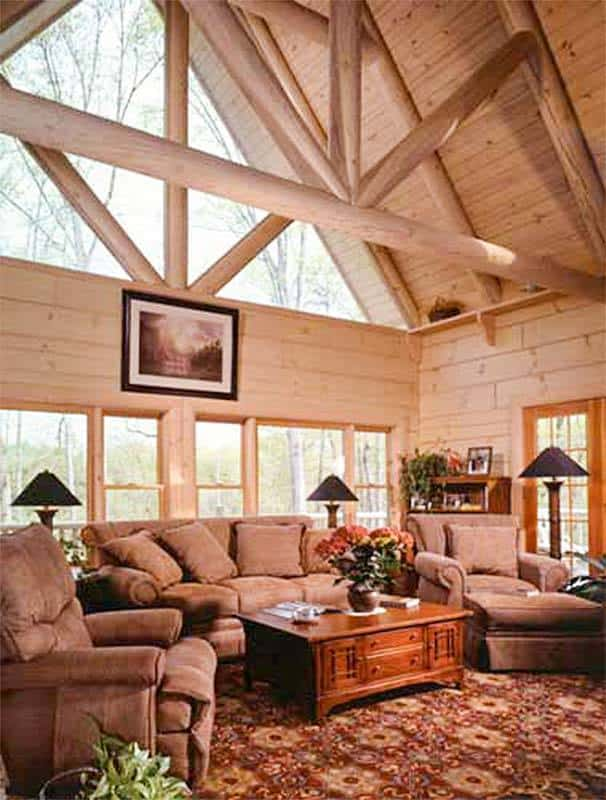 The living room features cathedral beam ceiling, large windows, and access to the deck.