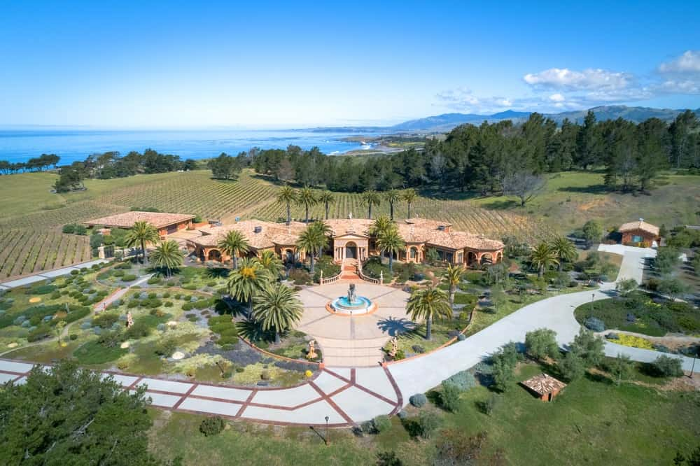This aerial shot of the whole property shows the large mansion with an earthy tone to its exterior standing out against the lush greenery of the large front yard and vineyard behind. Images courtesy of Toptenrealestatedeals.com.