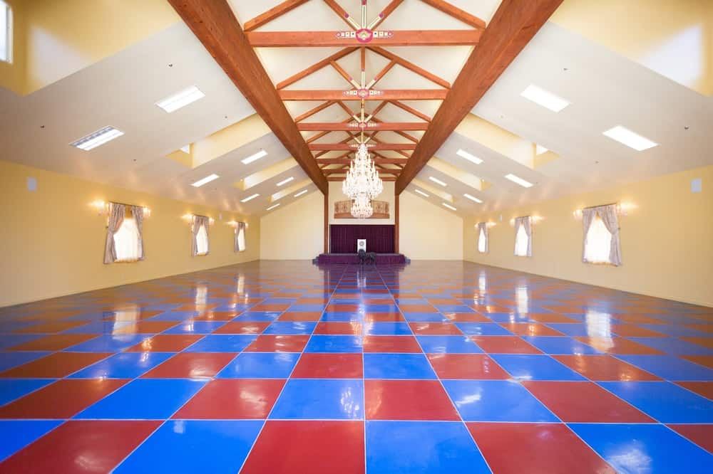 This massive ball room has colorful red and blue checkered flooring to contrast the beige walls and arched ceiling that has exposed wooden beams. There is also a raised stage area at the far end of the large room. Images courtesy of Toptenrealestatedeals.com.
