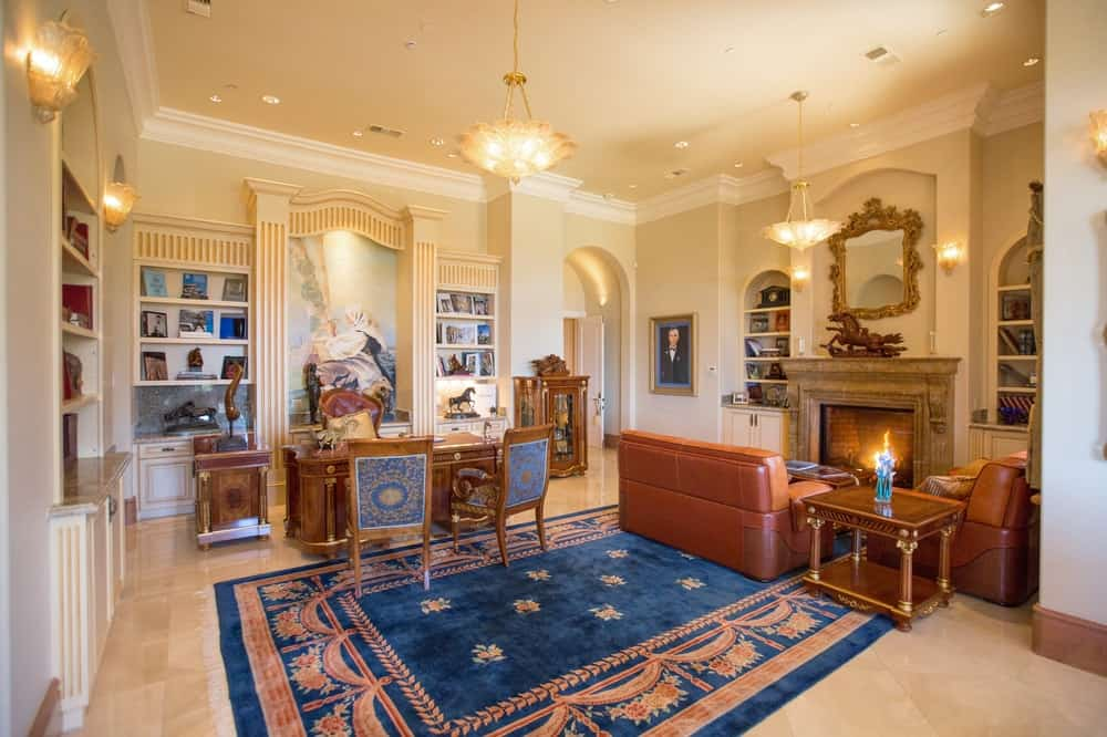 The charming den and home office of the mansion has an antique wooden desk paired with beautiful chairs. Beside this is a leather couch facing the large fireplace that is adorned with an elegant wall-mounted mirror above it. Images courtesy of Toptenrealestatedeals.com.