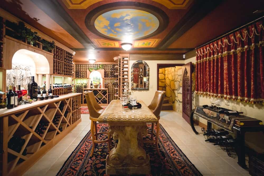 This 3,500-bottle wine cellar has a wine-tasting area with a marble table paired with cushioned stools over a colorful patterned area rug. This has a beautiful background of wooden shelves filled with wine bottles. Images courtesy of Toptenrealestatedeals.com.