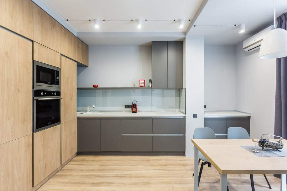 This is a view of the modern kitchen that has a large wooden structure on one side matching the flooring that gives complement to the gray cabinetry of the kitchen.