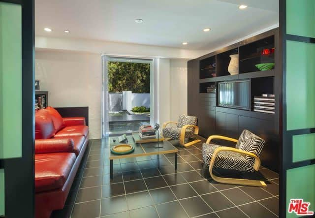 This lovely living room has black flooring tiles that match with the black wooden structure that houses the TV along with cabinets and shelves across from the red leather sofa set.