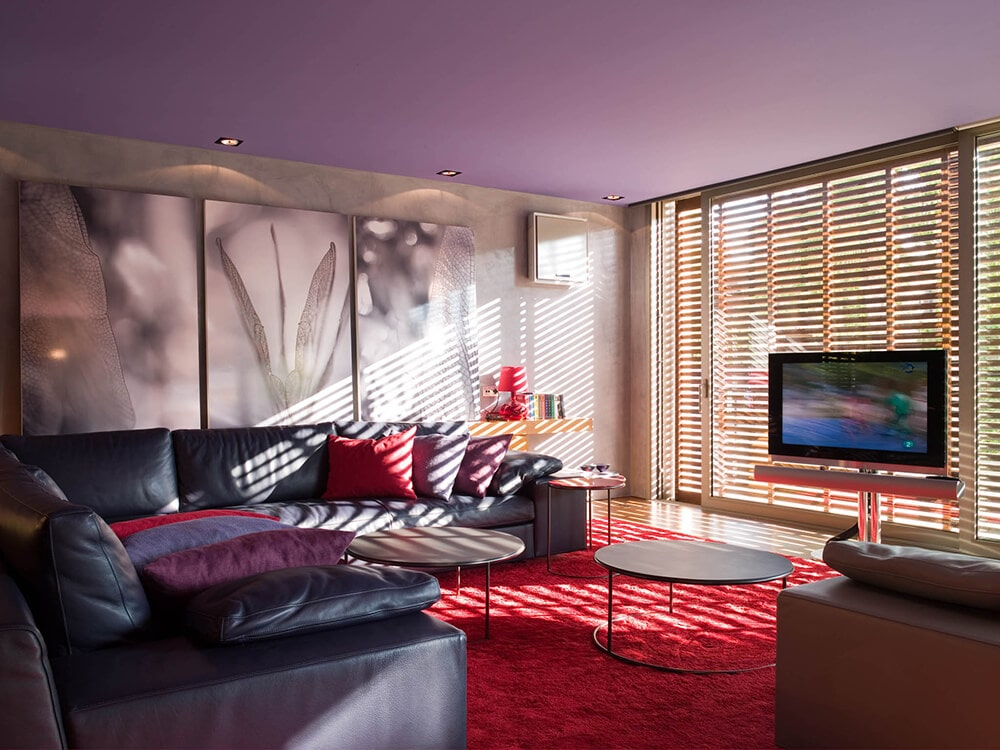 The homey living room is dominated by a large vibrant red area rug that gives a nice contrasts to the large black leather sectional sofa with matching red pillows under a large purple ceiling.