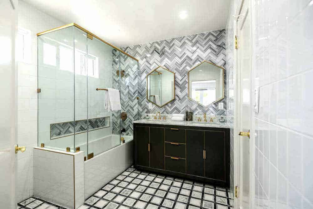 Here's a look at the bedroom suite's personal bathroom, featuring stylish walls and floors, along with a nice sink counter and a shower and bathtub combo