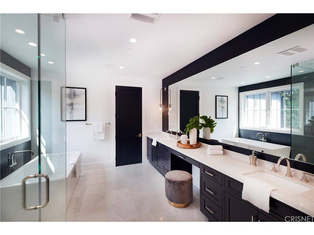 Black and white primary bathroom with a freestanding tub and a dual sink vanity paired with a round velvet ottoman. It is illuminated by recessed ceiling lights along with natural light flowing in from the white-framed windows.